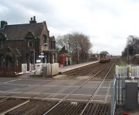 The original L&YR station building, now a private residence, still stands on New Lane's Up Platform. In front is a small waiting shelter and a traditional telephone kiosk. A Northern 142 Pacer, on a Southport to Wigan and Manchester service, hurries towards Burscough Bridge in this view across the level crossing from the staggered Down platform. <br><br>[Mark Bartlett&nbsp;17/03/2009]