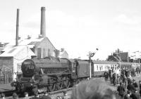 The LCGB <I>Lancastrian</I> railtour from Liverpool Lime Street, hauled by 45305 calls at Burscough Bridge on 6 April 1968 on its way to Southport. The junction signals above the third coach cover the north curve (left) towards Rufford & Preston, the line to Wigan (straight on) and the South Curve (right) towards Burscough Junction and Ormskirk. The chimneys and factory behind the locomotive have now gone. Behind the junction signal is the A59 road overbridge, from which the steps down to the eastbound (Wigan) platform are just visible.<br><br>[K A Gray&nbsp;06/04/1968]