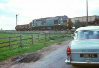 A smart looking Austin Cambridge is held at the level crossing at Cowpen Bewley, to the north east of Billingham in the 1960s, as a class 37 with brake-tender attached rumbles past with a coal train  heading for Teesside.<br> <br><br>[Bruce McCartney&nbsp;//]