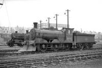 Looking across the running lines at a lineup of locomotives standing outside Bathgate MPD in April 1965, with snowplough-fitted Holmes J36 0-6-0 no 65267 to the fore. 76104 and 65282 stand in the background.   <br><br>[Robin Barbour Collection (Courtesy Bruce McCartney)&nbsp;16/04/1965]