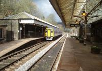 What a gem of a station Hebden Bridge is.  LYR period signage, canopies and replica gas lamps, working toilets, booking office and an excellent station buffet. 158872 stops at the staggered Up platform on a Manchester service.<br><br>[Mark Bartlett&nbsp;04/04/2009]