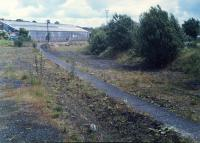 Looking east at Bathgate Upper. Bathgate Goods Yard was off to the left - a Landrover on a car train can be seen in the yard on the left. A new road had been built on the level which severed the old station from the still open line.<br><br>[Ewan Crawford&nbsp;//1988]
