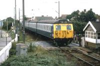 Frinton on Sea finally ceased to be a gated community in April 2009 when the level crossing on the only road access was converted to automatic barriers. This view of the crossing, taken on the evening of Sunday August 23rd 1981, shows a summer EMU service from Walton on Naze returning day trippers back up the line to Colchester.<br><br>[Mark Dufton&nbsp;23/08/1981]