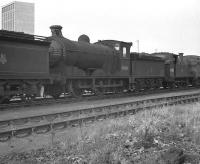 A line of <I>stored</I> locomotives, including 64466 and 69012, stand in the sidings at Thornton Junction MPD in the 1960s, with one of the towers enclosing the headgear of Rothes Colliery in the background.<br><br>[K A Gray&nbsp;//]