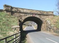 The twin railway bridges that cross the unclassified road over the North Yorkshire Moors, in the remote countryside between the A169 and the village of Goathland, photographed looking west on 20 April 2009. The nearest of the two bridges carries the current NYMR south from Goathland towards Levisham, while the bridge in the distance is on the original 1836 alignment, much beloved of horse-power and cable haulage, prior to its closure in 1865 in favour of the easier route.<br> <br><br>[John Furnevel&nbsp;20/04/2009]