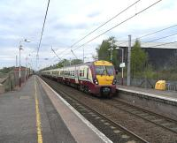 A 6-car 334 set pulls into Shieldmuir with the hourly Lanark direct service on 29 April. A new housing development is now underway on land off to the left once occupied by part of the former steelworks.<br><br>[David Panton&nbsp;29/04/2009]