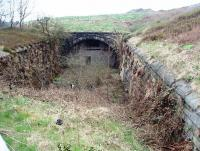 The south end of Newline tunnel on the steep climb to Britannia summit. Closed to regular traffic in 1947 the tunnel is now a vehicle workshop, accessed from the north side although there appears to be a fire escape door in this bricked up south portal.  Viewed from the A6066 Stacksteads to Bacup road at SD 877216 the buildings on the horizon overlook the north portal showing how shallow the land over the tunnel roof is. [See image 35969]<br><br>[Mark Bartlett&nbsp;16/04/2009]