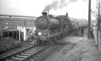 View north as class J37 no 64587 stands at Pomathorn at the head of the SLS <I>Farewell to Peebles</I> railtour on 3 February 1962, with the locomotive straddling the level crossing over the B6372. The imposing building in the background is the former Pomathorn paper mill, currently (2009) in use as a storage facility. Pomathorn station closed in 1962 and is now a private house [see image 6277].  <br> <br><br>[K A Gray&nbsp;03/02/1962]