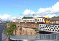 A westbound EMU heads for Partick on the urban viaduct alongside the Clydeside Expressway at Queens Dock on 10 May 2009. <br> <br><br>[Colin Miller&nbsp;10/05/2009]