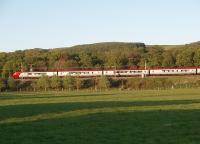 The setting sun lights up a northbound Voyager as it leans into a curve just south of the site of Scorton station. The M6 motorway is immediately behind the train, but thankfully screened by the trees so only the Bowland hills can be seen. <br><br>[Mark Bartlett&nbsp;11/05/2009]