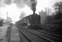 BR Standard class 9F 2-10-0 no 92097, having taken on WD 2-8-0 no 90434 as banker at South Pelaw, climbs through Beamish on an overcast Saturday 15 February 1964 with iron ore destined for Consett. By the time the train reaches its destination, it will have lifted its load from the import terminal at Tyne Dock bottom, on the south bank of the river, to the steel town, on the eastern edge of the Pennines, one thousand feet above sea level and, along the way, will have overcome gradients of up to 1 in 35. <br> <br><br>[Robin Barbour Collection (Courtesy Bruce McCartney)&nbsp;15/02/1964]