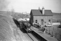 62471 <I>Glen Falloch</I> arrives at Gordon, Berwickshire, from Greenlaw, with the <I>Scott Country Rail Tour</I> on 4 April 1959. The station had been closed to passengers since 1948, although the goods yard is still active, with stone from local quarries being loaded in the background. The line from Ravenswood Junction was finally closed in 1965.<br><br>[Robin Barbour Collection (Courtesy Bruce McCartney)&nbsp;04/04/1959]