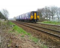 150223 heads west towards Southport on a service from Manchester Victoria on 3 April 2009. The train has just left Burscough Bridge station which can be seen in the distance. <br> <br><br>[John McIntyre&nbsp;03/04/2009]
