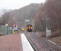 The eastern approach to Connel Ferry, formerly a three platform junction station but now just a plain single line with a short siding. The sidings in the oil depot alongside the platform are now lifted. The remaining siding is seen here occupied by a civil engineering machine that had probably been used in connection with the resleepering that could be seen in the station area. 156467 approaches heading for Oban.<br><br>[Mark Bartlett&nbsp;27/03/2009]
