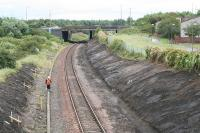 Looking east at the site of Bangour Junction in August 2007. The overbridge which now carries the A899 over the railway is the location of a signalbox associated with the branch which diverged in a north westerly direction immediately to the east of the overbridge, before it looped back on itself then once again reversed at the village of Dechmont before following a westerly route to it's terminus. A short lived private line, it existed to serve the hospital of the same name. The scrubland to the left contained a set of sidings associated with the branch, and a sizeable headshunt existed extending almost to the overbridge at Nettlehill. Most of the remains of the Bangour branch were obliterated with the A899 and M8 construction in this area.<br><br>[James Young&nbsp;01/08/2007]