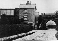 A very early picture of Scorton station, perched high on the WCML embankment. The wooden platform buildings can be seen alongside the stone built station house. The station closed on 1.5.39 and all trace has been swept away. [See image 23496] for a modern day comparison from the same viewpoint, looking west along Station Lane just outside the village. <br><br>[Rev Ron Greenall Collection&nbsp;//1900]