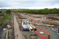 Looking North toward Bathgate town centre on 23 May 2009. A temporary road is under construction which crosses the bed of the <i>Bathgate and Coatbridge Railway</i> at the site of <i>Polkemmet Junction</i> to allow the replacement of the Whitburn Road overbridge in Bathgate. The solum of the railway is to the left of the image, while the treeline to the right marks the course of the <i>Wilsontown, Morningside and Coltness Railway</i><br><br>[James Young&nbsp;23/05/2009]