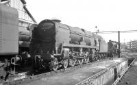 Bulleid <I>West Country</I> Pacific no 34005 <I>Barnstaple</I> in the yard at Nine Elms c 1965. The locomotive was withdrawn by BR in March of 1967, a few months prior to the final closure of the shed itself. The former 15 road shed with its large yard and adjoining goods depot is now the site of London's wholesale fruit and vegetable market. <br> <br><br>[K A Gray&nbsp;//1965]