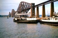 View of the Forth Bridge from South Queensferry in 1963, the year before the road bridge was opened. Two of the ferries which would be made redundant following the opening of the road bridge stand at Hawes Pier.<br> <br><br>[John Alexander&nbsp;//1963]