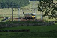 A northbound First TransPennine Express 185 rounds the curve approaching Elvanfoot on 1 June 2009. The photograph is taken from near the bottom of Station Road with the station site off to the left.<br><br>[John McIntyre&nbsp;01/06/2009]