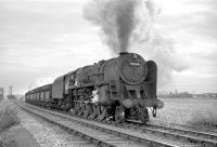 BR Standard Class 9F no 92064, carrying a 52H, Tyne Dock, shedplate, photographed near Pelton in the 1960s en route to Consett steel works with a trainload of imported iron ore. The train has recently picked up a banking locomotive at South Pelaw. Note the Westinghouse pumps for operating the hopper doors, fitted to all ten of the 9Fs based at Tyne Dock.<br><br>[Robin Barbour Collection (Courtesy Bruce McCartney)&nbsp;//]