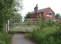 Originally a full vehicle crossing, but for many years restricted to pedestrians only, this is New Road on the mothballed Fleetwood Branch just south of Thornton-Cleveleys station. New Road is shown in Quails Track Diagrams as <I>Tarn Gate</I>. The crossing keeper's cottage is in private ownership and at the time of this photograph was <I>For Sale</I>. <br><br>[Mark Bartlett&nbsp;10/06/2009]
