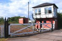 The level crossing and signal box at Holywood, on the G&SW route north of Dumfries, seen here looking east on 10 June. Holywood is one of the reducing number of crossings in the UK where the gates continue to be operated manually by the signalman, using a wheel located within the box.<br> <br><br>[David Forbes&nbsp;10/06/2009]