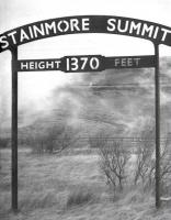 View from a train - 1962. Photograph taken from <I>The Stainmore Limited</I>, as 77003+76049 haul the 9 coach special over Stainmore summit, commemorating the end of operations on the line. The <I>South Durham and Lancashire Union Railway</I> route across the Pennines was notorious for snow blockages in winter with a summit height of 1,370 ft (compared with Shap at 914 ft and Beattock at 1,033 ft) placing it between Slochd (1315 ft) and Britain's highest main line summit at Druimuachdar (1484 ft). The old cast iron summit signs are now preserved, one at the NRM in York, the other at North Road Museum in Darlington.<br><br>[K A Gray&nbsp;20/01/1962]