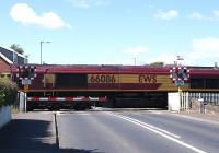 EWS 66086 makes its way over the Level Crossing at the village of Gatehead, Ayrshire, on 12 June 2009. Located on the single line section between Kilmarnock and Barassie, Gatehead station closed in March 1969.<br> <br><br>[David Forbes&nbsp;12/06/2009]