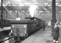 J36 0-6-0 no 65234 stands in a bay platform at the east end of Waverley with a railtour on 29 August 1964. The train, made up of ex-<I>Talisman</I> coaching stock and carrying reporting code 100, visited various branch lines in and around Edinburgh and the Lothians including North Leith, Haddington and Penicuik. The tour had been jointly organised by the SLS/BLS with the objective of raising funds towards securing and preserving an example of the J36 class. The figure standing to the right of the locomotive is the late Bob Mitchell, Traction Inspector. [This image has been rerun with additional information kindly provided by David Kerr, whose late father David G Kerr accompanied this and many other railtours in the 1960s in his role as District Operating Inspector. Ed]<br> <br><br>[K A Gray&nbsp;29/08/1964]