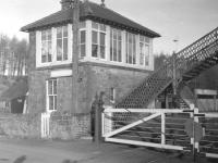 The signal box and level crossing at Newcastleton station on the Waverley route, seen here in the early sixties. A fairly quiet and peaceful location, apart from one particular night in 1969. [See image 18723]   <br><br>[Robin Barbour Collection (Courtesy Bruce McCartney)&nbsp;//]