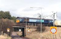 A container train, hauled by DRS 66412, crosses Lampits Road on the approach to Carstairs station on the ex-Caledonian route from Edinburgh in March 2007. The train has travelled via the ECML and the <I>sub</I> and has just over 30 miles still to go on its journey to WHM, Grangemouth. <br><br>[John Furnevel&nbsp;08/03/2007]