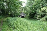 The east end of Hincaster tunnel under the WCML (which can just be made out above the tunnel entrance). Although this looks like a single track railway tunnel, it is in fact part of the abandoned Lancaster Canal which formerly operated between Preston and Kendal. The tunnel was constructed during 1816 & 1817 and is 378 yards long. Over 4 million bricks were used in the construction of the tunnel and in its day was the first major brick structure north of the River Mersey. The path to the left also leads under the WCML, over the hill and to the west side of the tunnel. It was used by the horses that pulled the barges on the canal as there was no towpath through the tunnel. The last commercial traffic passed through the tunnel in 1944. See also photos 21298 and 21302. This is a key point on yesterdays and todays transport networks as the A590 dual carriageway also passes under the WCML approx 50 yards to the right of the picture.<br><br>[John McIntyre&nbsp;20/06/2009]