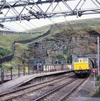 EM1 no 76046 exits the western portal of Woodhead Tunnel with a freight on 15 August 1979. The train is about to pass the marker board  for platform 4 at Woodhead station, which had closed to passengers in July 1964. Built in 1952 as 26046, the locomotive carried the name <I>Archimedes</I> until the late 60s and was withdrawn in November 1980. <br><br>[Peter Todd&nbsp;15/08/1979]