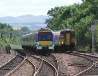 An Aberdeen express passes a recessed <i>Fife circle</i> Class 150 at Dalmeny on 21 August 2004.<br><br>[James Young&nbsp;21/08/2004]