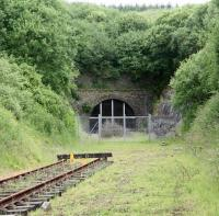 Located approximately 12 miles south of Hawick, between Shankend and Riccarton Junction, is the 1,208 yard Whitrope Tunnel, the south portal of which is seen here on 10 July 2009. The tunnel, noted as Scotland's fourth longest, is currently a listed structure (Category B). The rails in the photograph represent the northern extent of the relaying undertaken by the Waverley Route Heritage Association, whose volunteers have carried out considerable work associated with the tunnel and the Whitrope site in general. The WRHA centre and car park is located alongside the B6399 road just to the south of this point. [See image 32810]<br> <br><br>[John Furnevel&nbsp;10/07/2009]