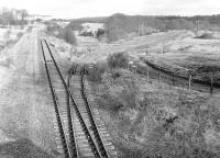 The Moffat Mills branch, east of Airdrie, survived to carry grain traffic to Inverhouse Distillery until the mid 1980s. View is east over the junction from the road bridge in February 1988, looking along the remains of the Airdrie - Bathgate line between Clarkston (Lanarks) and Plains with the trackbed of the Moffat Mills branch running off to the right. [See image 25408] <br> <br><br>[Bill Roberton&nbsp;21/02/1988]