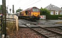 EWS 67011 westbound over Kingsknowe level crossing on a wet Saturday morning heading for Polmadie with the empty stock of the Edinburgh portion of the Lowland Sleeper.<br><br>[John Furnevel&nbsp;18/07/2009]