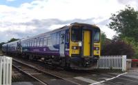 153304 leads an unusual 3-car combination on a Northern service from Carlisle to Whitehaven at Low Mill level crossing Dalston, Cumbria, on 22 July 2009. The unit would appear to have a problem with its lights.<br><br>[Brian Smith&nbsp;22/07/2009]