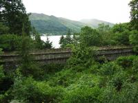 Beneath all the greenery near St Fillans is this four span viaduct over a steep gorge with a fast flowing burn. Loch Earn can be seen in the middle distance with a caravan park beyond. <br><br>[John Gray&nbsp;30/07/2009]