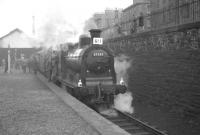 Platform view east towards the buffer stops at Leith North on 3 February 1962 as Dalry Road shed's 57550 prepares to depart with the <I>Peebles Railtour</I>. The proceedings are being watched with interest by a group of young enthusiasts from behind the iron railings on Lindsay Road.<br><br>[K A Gray&nbsp;03/02/1962]