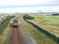 The line between Squires Gate and the outskirts of St Annes passes through an open area of sand dunes where Blackpool Airport and the St Annes Old Links Golf Club are also situated. 142007 is on a Blackpool South to Colne service and the distinctive Blackpool skyline can be seen behind the train as it runs towards St Annes station. <br><br>[Mark Bartlett&nbsp;11/08/2009]