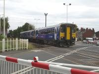 Northern Rail's 15.07 service to Wakefield Kirkgate comprising single unit 153301 leading a Class 150/2 DMU departs Streethouse Station over Whinney Lane level crossing   <br><br>[David Pesterfield&nbsp;14/08/2009]