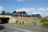 A First Trans-Pennine Express service for Manchester Airport leaves the WCML at Euxton Junction and heads to Manchester via Chorley and Bolton on 7 August 2009. The road in the foreground is the A49 former trunk road which passes under the WCML through a two part bridge. The older part (dating from the opening of the railway?) is known as Pack Saddle Bridge and is so narrow that traffic has to be controlled by traffic lights. It has also suffered from being struck on several occasions by road vehicles due to restrictions on height as well as width.<br><br>[John McIntyre&nbsp;07/08/2009]