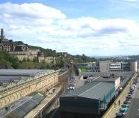 View east from Edinburgh's North Bridge on a sunny 24 August 2009.  The south wall of Waverley station stands on the left with <I>sub</I> platforms 8 and 9 alongside. In the centre background the 1220 from North Berwick has just left the Calton Tunnel and is running into platform 4. The bright green patch in the centre of the picture is the grass roof of the Edinburgh Council HQ, complete with <I>grazing</I> fibreglass cow. In the foreground is the Edinburgh signalling centre with the 2006 IECC extension nearest the camera and the original 1977 building beyond. The Firth of Forth can be seen above the Edinburgh Council building, with two of the floodlights of Meadowbank stadium breaking the horizon to the left and the twin chimneys of Cockenzie power station in the right background. <br> <br><br>[F Furnevel&nbsp;24/08/2009]