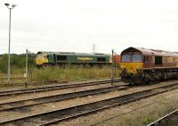Freightliner 66572 overtakes EWS 66168 alongside Didcot Parkway station on 18 August 2009 as it turns north with a freight on the avoiding line heading towards Oxford.<br><br>[Peter Todd 18/08/2009]