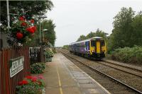 A stopping eastbound service from Southport to Manchester Victoria slows for Bescar Lane station in West Lancashire on 26 August 2009. The station has received a lot of attention from the station adoption group with very attractive and colourful display of flowers on both the Southport platform and, behind the camera, the Manchester platform on the other side of the level crossing.<br><br>[John McIntyre&nbsp;26/08/2009]