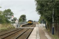 The staggered platforms, separated by a level crossing, is a common feature of West Lancashire stations on the Wigan to Southport line. Here at the very rural New Lane station a Southport bound service is seen passing the down platform on 26 August 2009. <br><br>[John McIntyre&nbsp;26/08/2009]