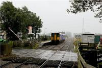A very wet afternoon at Hoscar station as a Southport to Manchester service rushes through on 26 August 2009. The train is not stopping at this rural station and the level crossing barrier is already lifting to allow road traffic to move on Hoscar Moss Road. Just out of shot to the left of the photo is the Railway public house, a very useful place to retreat to on such a miserable day!<br><br>[John McIntyre&nbsp;26/08/2009]