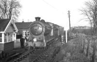 Class J37 0-6-0 no 64587 pauses on the crossing alongside Rosslynlee station on 3 February 1962 on its way south with the <i>Farewell to Peebles</I> railtour over the Peebles loop. The line was closed to passenger traffic south of Hawthornden Junction two days later. District Operating Inspector David G Kerr, who accompanied many of these specials, is standing on the left of the picture with his back to the crossing gates. <br><br>[K A Gray&nbsp;03/02/1962]